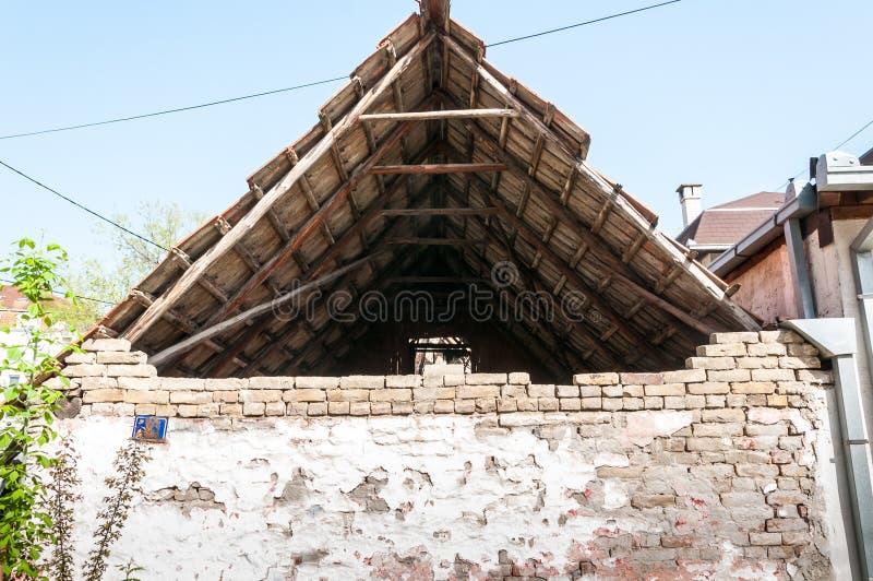 Altes verlassenes und schädigendes Haus mit Dachplatten und weißer Wand mit gebrochenem Gips auf dem Ziegelsteinhintergrund lizenzfreie stockbilder