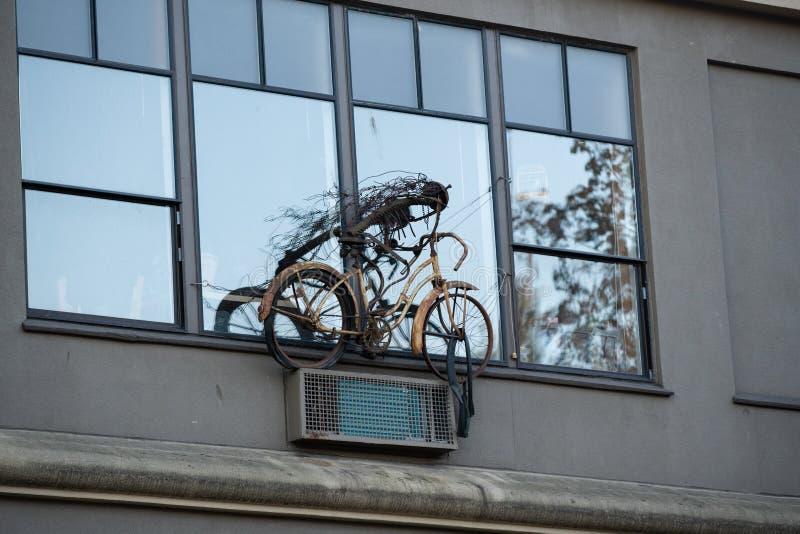 Altes verrostetes Fahrrad, welches das Fenster verziert stockbilder