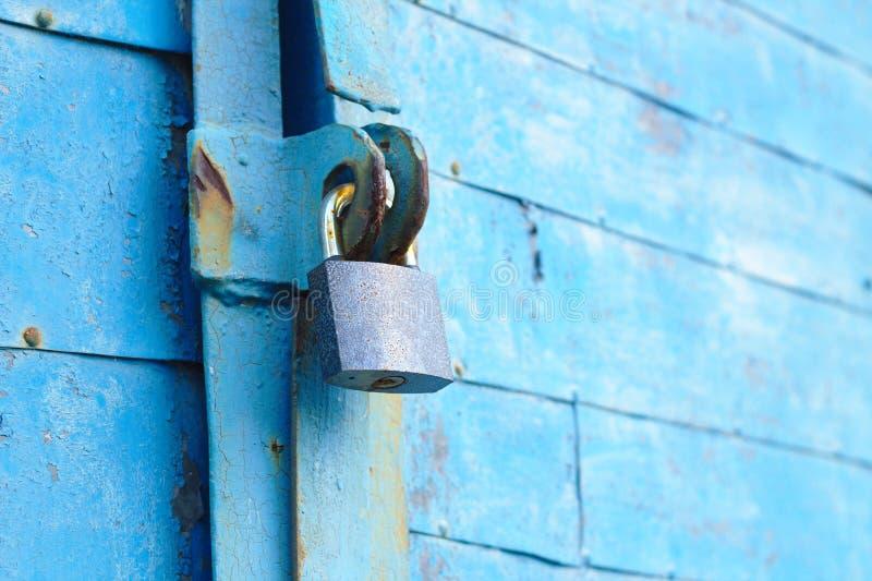 altes Vorhängeschloß auf einer blauen Metalltür mit hölzernen Planken knackte Farbe und Rost lizenzfreies stockfoto
