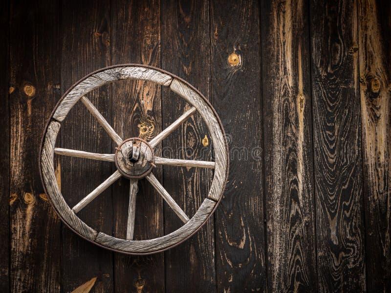 Altes Wagenrad, das an einer hölzernen Scheune hängt stockbild