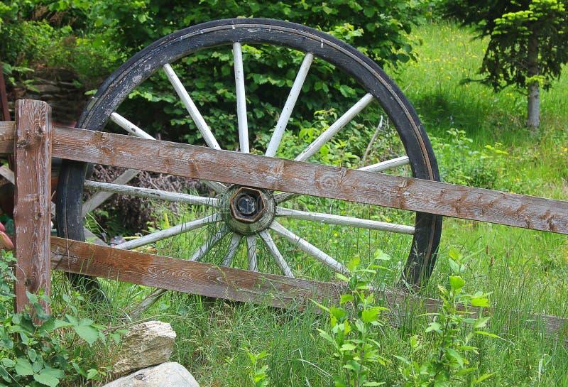 Altes Wagenrad nahe einem Bretterzaun stockfoto