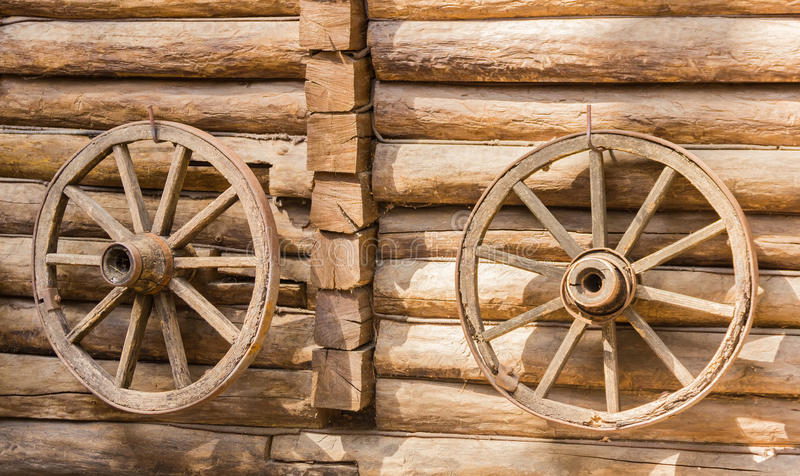 Altes Wagenrad zwei auf einer hölzernen Wand lizenzfreies stockfoto