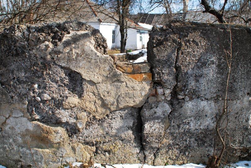 Altes weißes Gebäude mit Bäumen hinter ruiniertem Zaun lizenzfreies stockbild