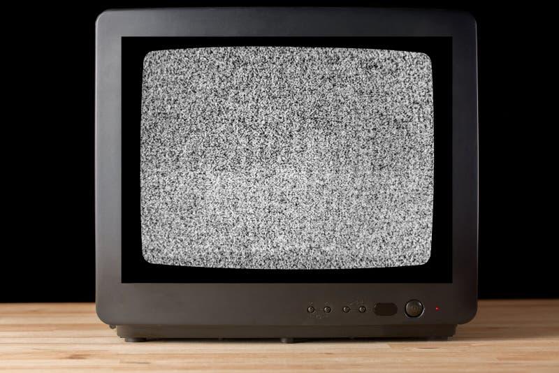 Altes Weinlese Fernseher televisor auf Holztisch againt Schwarzhintergrund ohne Signalfernsehkörnigen Geräuscheffekt auf den Schi stockbild