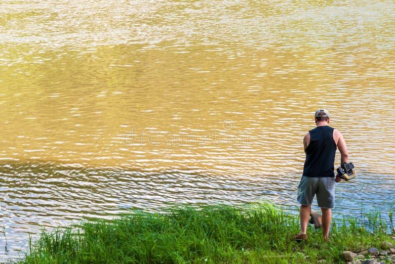 Althom, Pensilvania, U.S.A. 8/10/2019 di uomo di A facendo uso di un whacker dell'erbaccia a per sistemare erba lungo il fiume di fotografie stock
