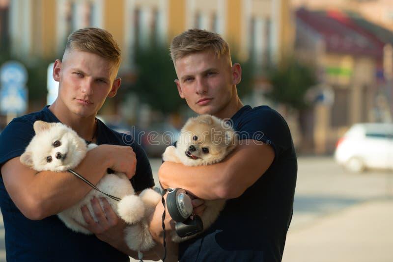 Altijd gelukkig samen Spiermensen met hondhuisdieren Gelukkige familie op gang De tweelingenmensen houden rashonden Gelukkige twe royalty-vrije stock foto's