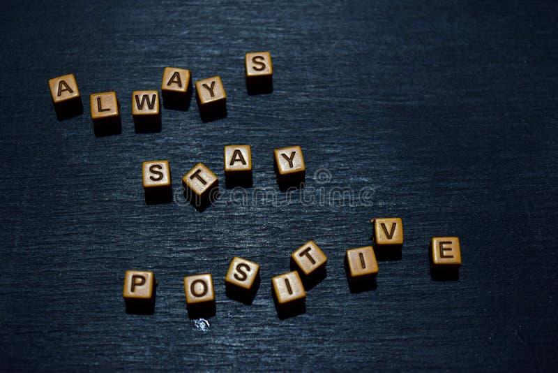 Altijd verblijfs positief die bericht op houten blokken wordt geschreven Motivatieconcepten Kruis verwerkt beeld royalty-vrije stock foto