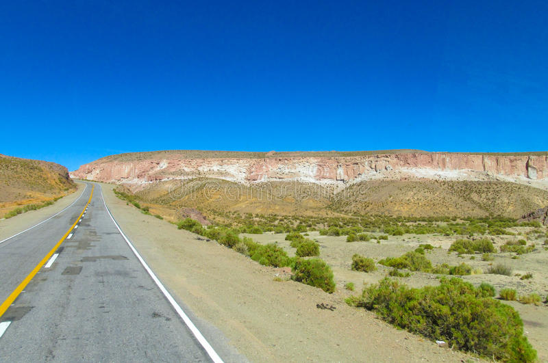 Altiplano desert arid landscape and asphalt road. From Argentina to Chile stock photography
