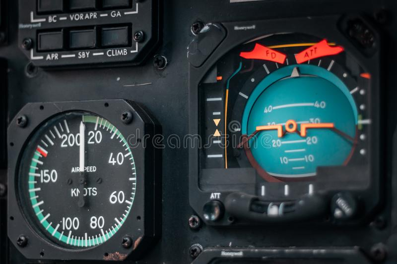 Details of control panel in military helicopter cockpit. Altitude and other major instruments on the panel of a military cockpit. Black metal frames and glowing royalty free stock photo