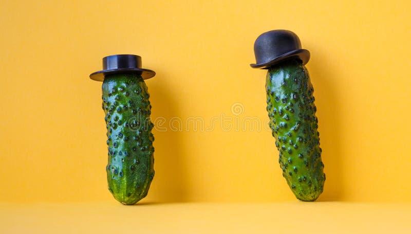 Altmodische Charaktere der lustigen Gurken mit schwarzen Hüten gelber Hintergrund, kreatives Designlebensmittelplakat lizenzfreies stockfoto