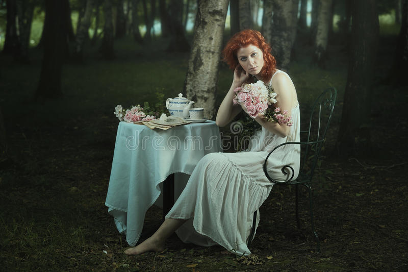 Altmodische Frau, die im träumerischen Holz aufwirft lizenzfreies stockfoto