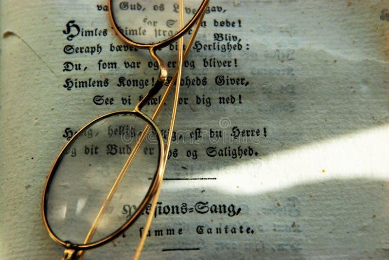 Altmodische Gläser mit einem Buch stockbild