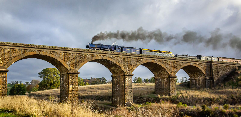 Altmodischer Dampf-Zug, der eine historische Blaukugel-Maurerarbeit-Brücke, Malmsbury, Victoria, Australien, im Juni 2019 kreuzt lizenzfreies stockfoto