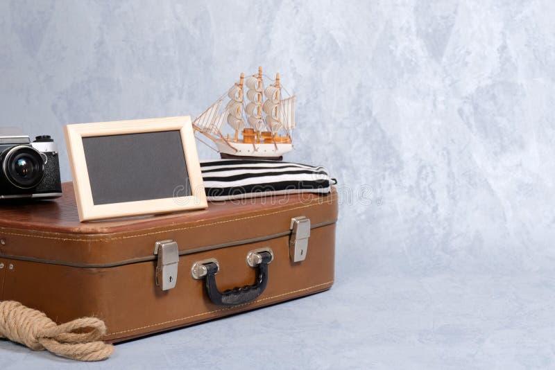 Altmodischer lederner Koffer, Bilderrahmen mit leerem schwarzem Raum für Text, Segelbootspielzeug, Retro- Fotokamera, Seil stockfotografie