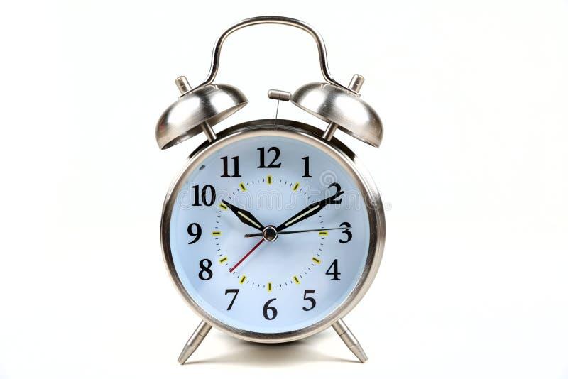 Altmodischer Wecker des Edelstahls auf einem weißen Hintergrund lizenzfreie stockfotografie