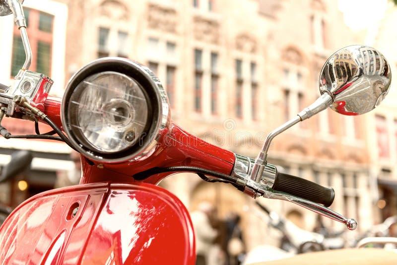 Altmodisches rotes Motorrad geparkt im Stadtzentrum stockbild