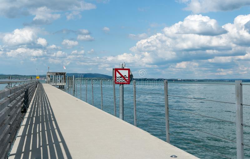 Close up view of  the long pier at Altnau on Lake Constance with a no swimming sign because of passenger ship traffic routes royalty free stock images
