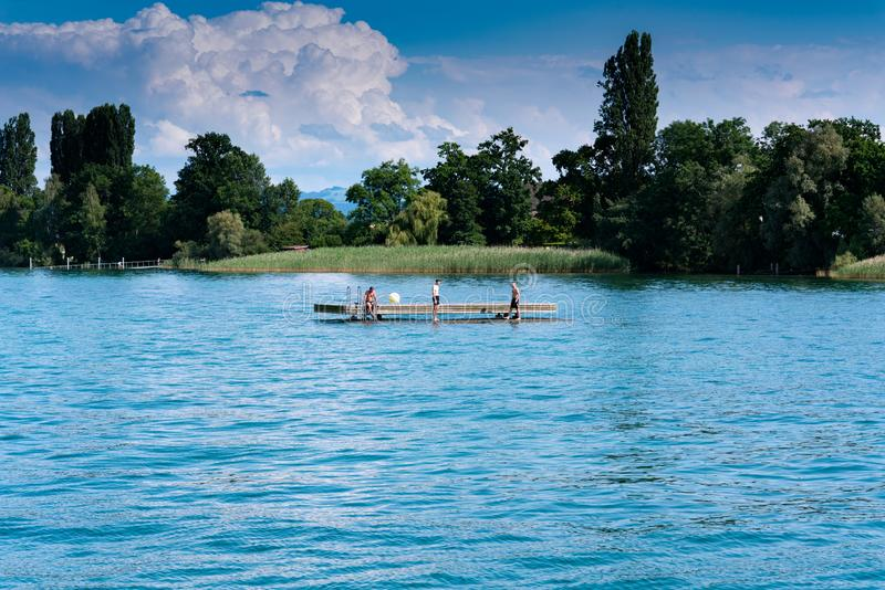Young men relaxing and swimming on a wooden swimming platform in a large lake. Altnau, TG / Switzerland - 14. July 2019: people relaxing on a wooden swimming royalty free stock images