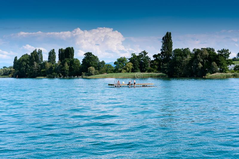 Young men relaxing and swimming on a wooden swimming platform in a large lake. Altnau, TG / Switzerland - 14. July 2019: people relaxing on a wooden swimming stock image