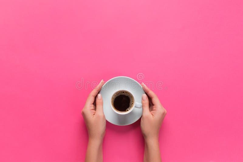 Alto ángulo de las manos de la mujer que sostienen la taza de café en el estilo rosado de Minimalistic del fondo La endecha plana fotos de archivo libres de regalías