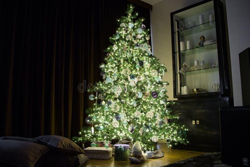 Alto árbol de navidad con los ornamentos y las guirnaldas imagenes de archivo