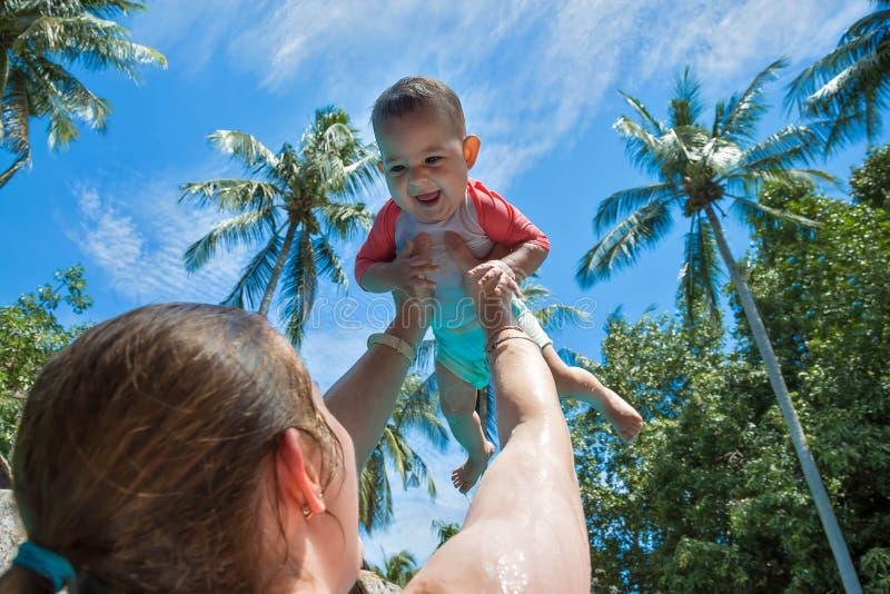 Alto aumentado mamá del bebé sobre la cabeza en la piscina La ni?a es muy feliz y gritos para la alegr?a Vacaciones de verano, pa fotos de archivo