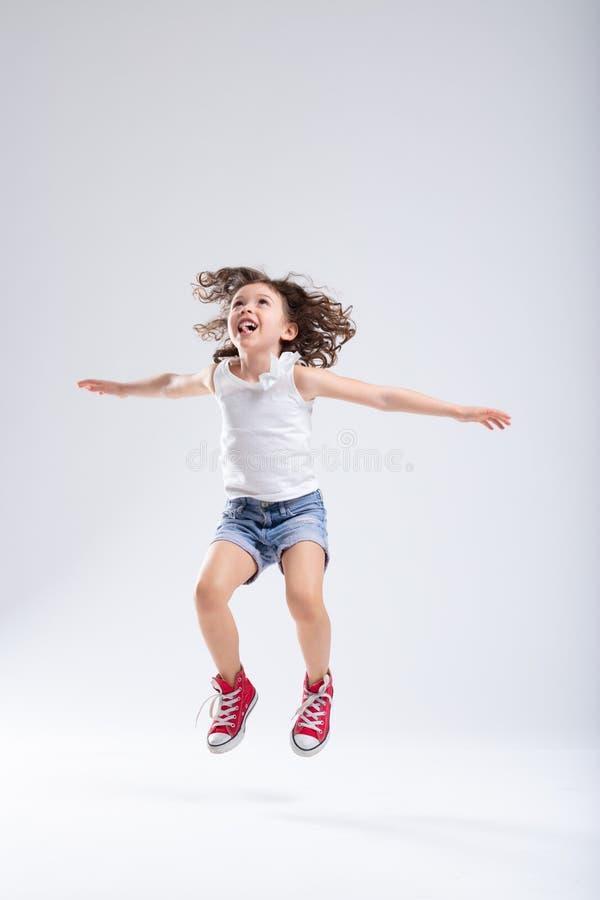Alto de salto de la niña activa enérgica alegre imagen de archivo libre de regalías