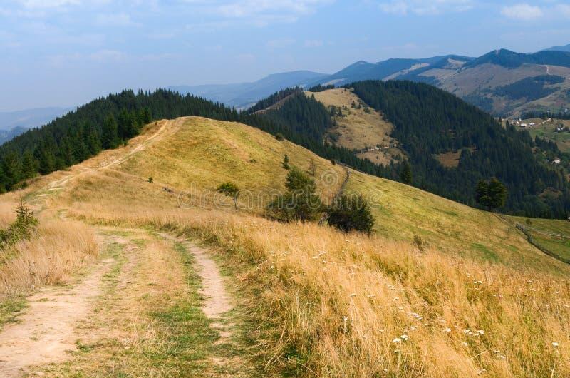 Alto del camino de tierra en las monta?as que va abajo al pueblo en el valle fotografía de archivo