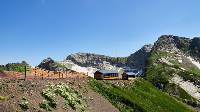 Alto del servicio de rescate de la montaña de los edificios en las montañas Nieve en verano en las cuestas de las montañas imagen de archivo