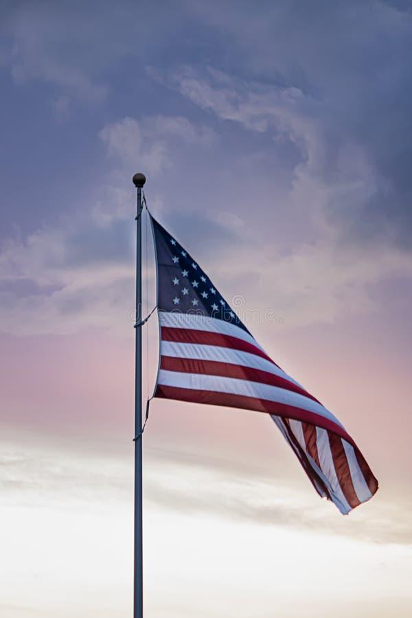 Alto del vuelo de la bandera americana en cielo nublado durante la primavera contra azul y rosado fotografía de archivo