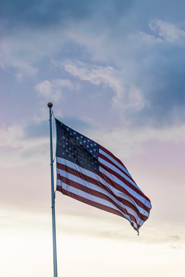 Alto del vuelo de la bandera americana en cielo nublado durante la primavera contra puesta del sol imágenes de archivo libres de regalías