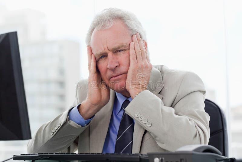 Alto directivo cansado que trabaja con un monitor fotos de archivo