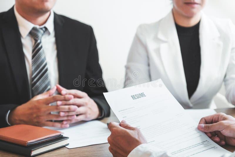 Alto directivo hora que lee un curriculum vitae durante un candidato y un reclutamiento de la reunión del hombre joven del emplea foto de archivo