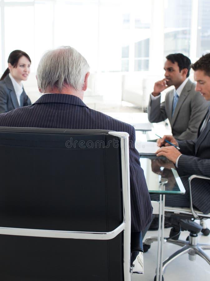 Alto directivo visto de detrás en una reunión fotos de archivo