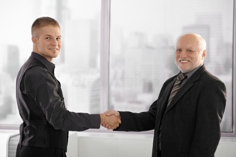 Alto executivo que agita as mãos com empregado novo fotos de stock