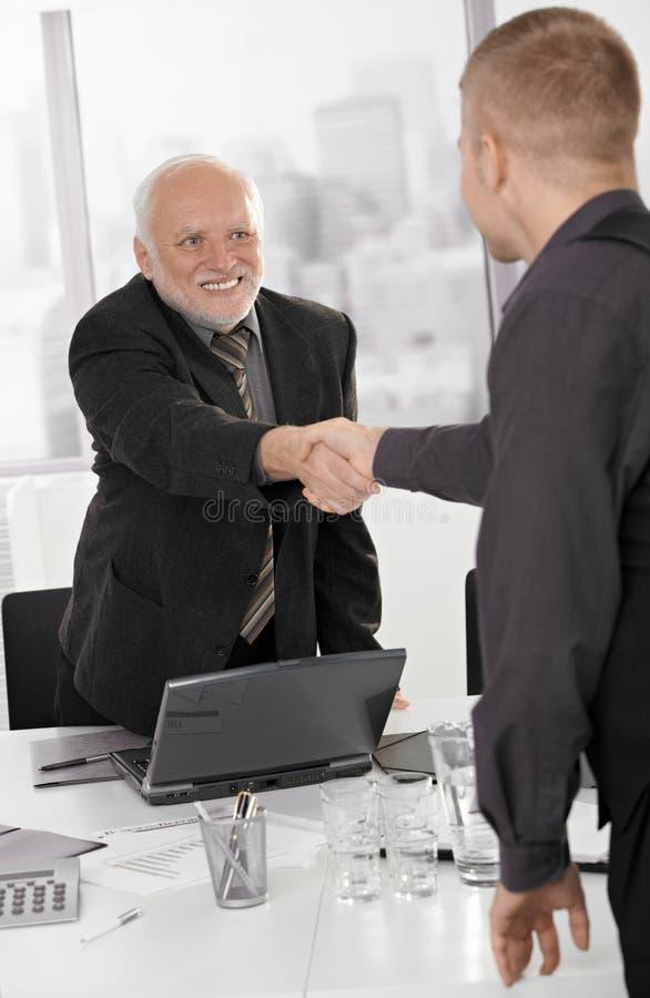 Alto executivo que agita as mãos com homem de negócios foto de stock royalty free