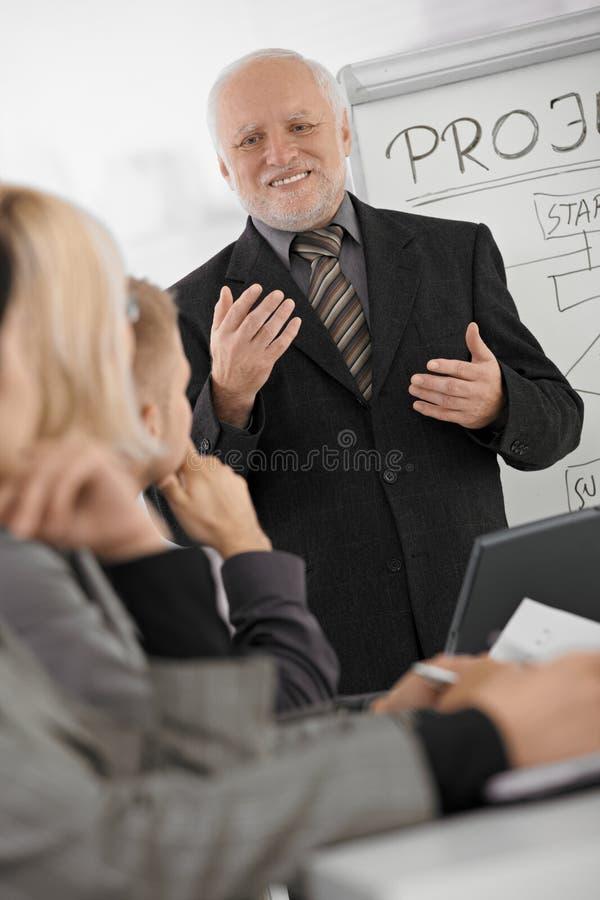 Alto executivo que explica o trabalho aos colegas. imagens de stock royalty free