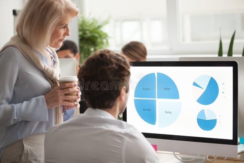 Alto executivo que verifica o informe anual no helpi do tela de computador fotografia de stock