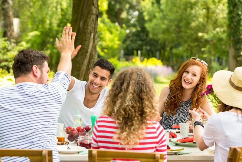 Alto fiving di due amici mentre sedendosi alla tavola durante il Gard fotografie stock libere da diritti