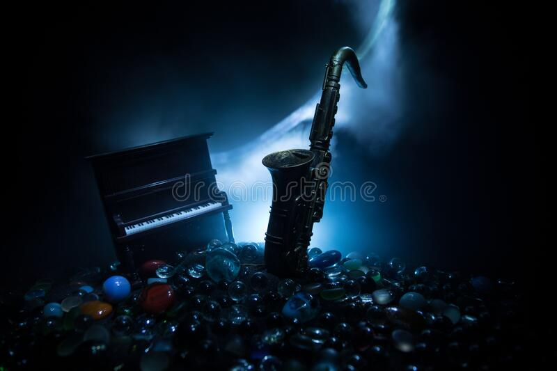 Alto gold sax miniature with colorful toned light on foggy background. Saxophone music instrument in lowlight. Selective focus. Music concept. Saxophone jazz stock image