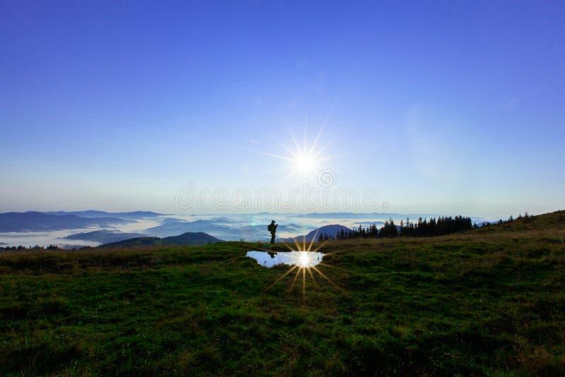Alto nas montanhas acima das nuvens um homem novo está procurando uma conexão celular que guarda seu telefone altamente fotografia de stock