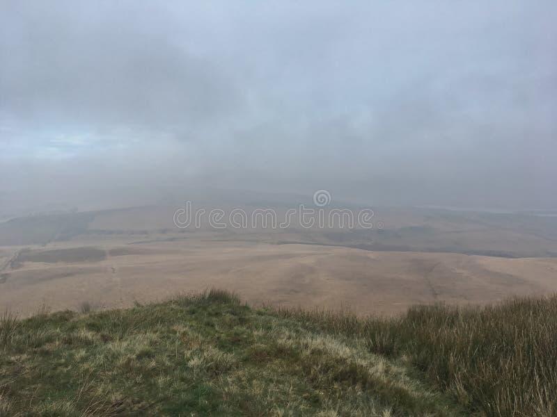 Alto nelle colline che esaminano giorno nuvoloso/nebbioso di vista del campo, contenuto il Regno Unito fotografia stock libera da diritti