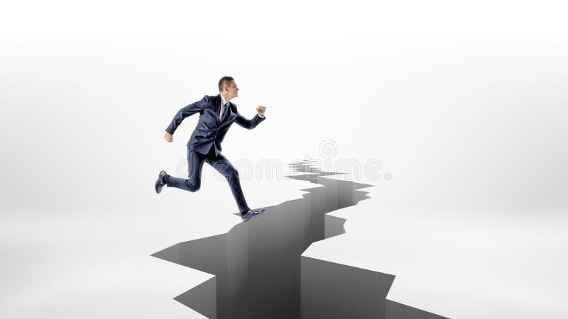 Alto-saltos de un hombre de negocios sobre una grieta dentada larga del terremoto en la tierra foto de archivo