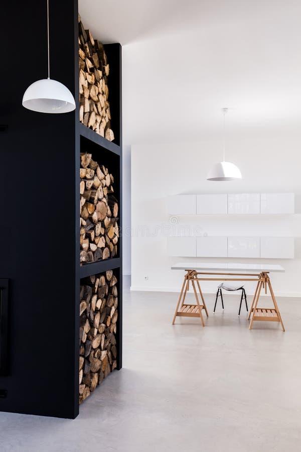 Alto scaffale per immagazzinare lo scrittorio dell'interno e minimalista della legna da ardere fotografie stock libere da diritti