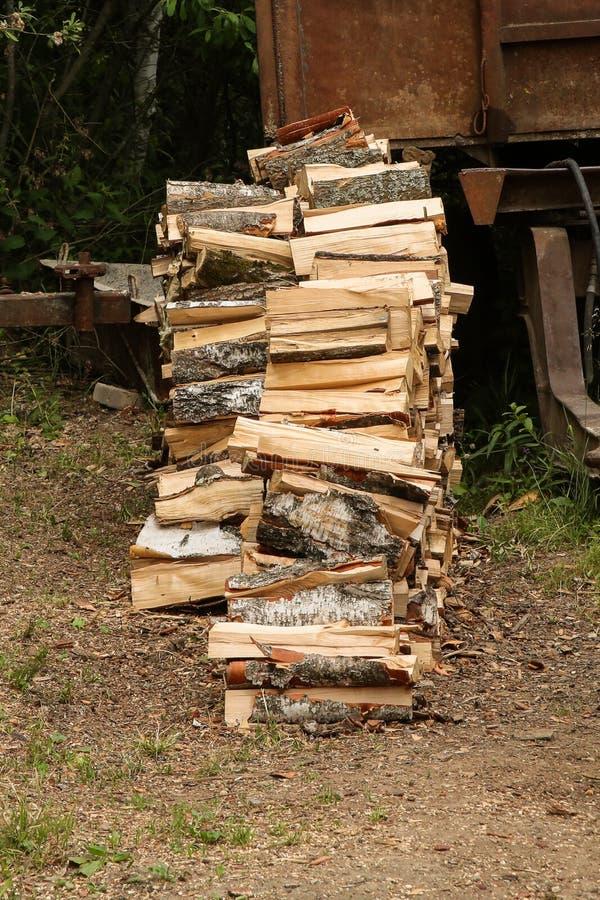 Alto tajado pila de la pila de la leña del abedul en perfil en el fondo de tierra seco que almacena la chimenea del invierno de l foto de archivo