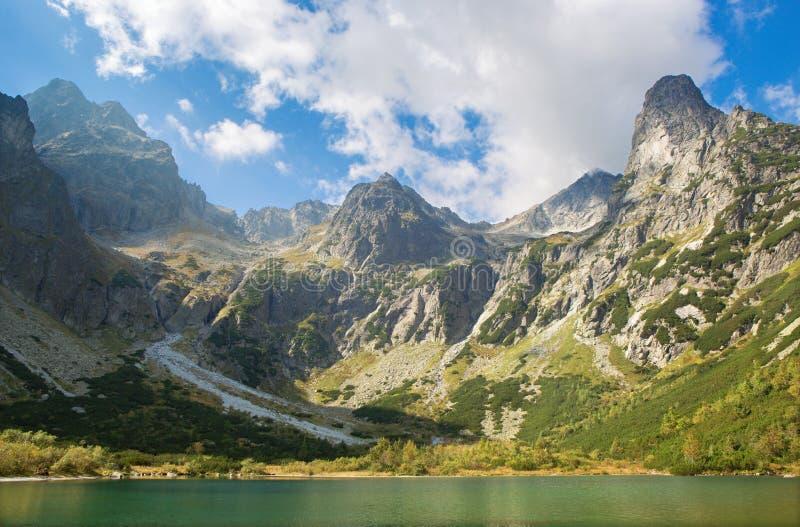 Alto Tatras - il lago e la valle Zelene Pleso con il picco di Pysny e la torre di Jastrabia ed altri picchi fotografia stock libera da diritti