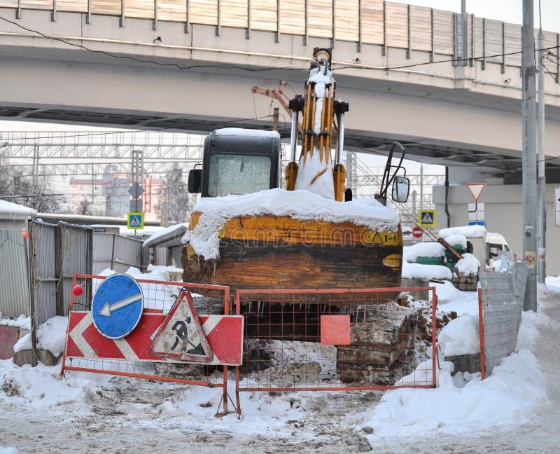 Alto vicino dell'escavatore Lavoro di riparazione nell'inverno sulla via La Russia fotografia stock libera da diritti