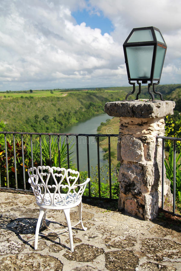 Altos de Chavon cafe with view on tropical river. Old chair in Altos de Chavon cafe with view on tropical river royalty free stock images
