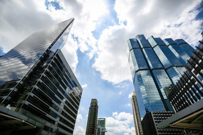 Altos edificios de la subida y cielo azul Rascacielos con la fachada de cristal Edificios modernos en el distrito financiero de T imagen de archivo