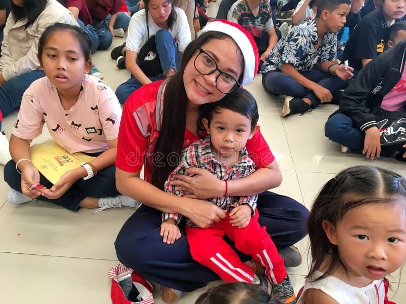 Altri e suoi bambini tailandesi tra altri bambini che celebrano evento di Natale a Bangkok, Tailandia 22 dicembre 2018 immagini stock